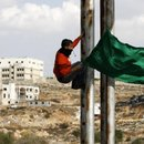Palestinian stone-throwers holds a Hamas flag as he climbs a street pole during clashes with Israeli security forces near Ramallah